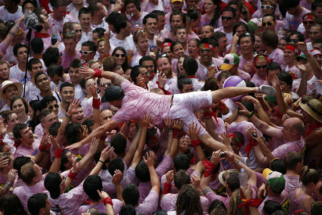 A reveller gets carried in the air by the crowd during the start of the San Fermin Festival in Pamplona
